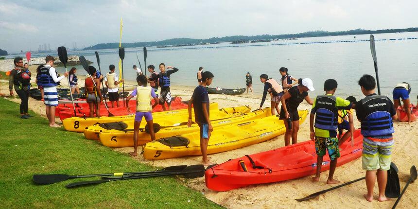 kayakers preparing to launch kayak to sea