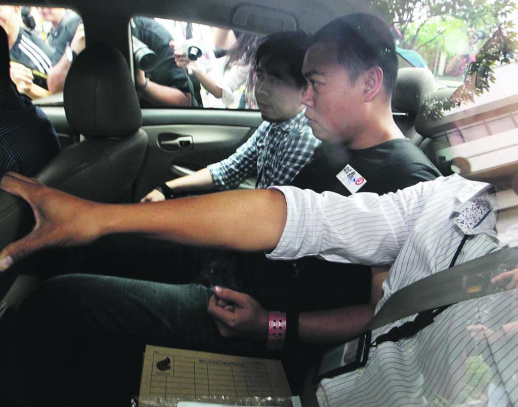 Murderer escorted in police car in Kovan murder