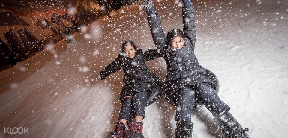 children sliding down slope at snow city Singapore