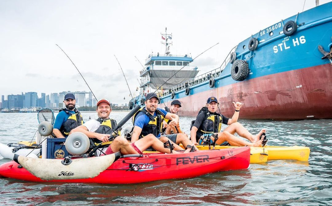 kayakers posing in front of a large ship in Singapore